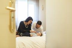 La maman et le papa ayant leur bébé obtiennent habillés pour une occasion spéciale Photo libre de droits