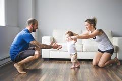 La maman et le papa gais aident leur fils à marcher à la maison photos libres de droits