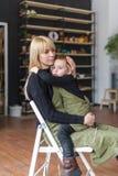 La maman et le petit fils s'asseyent dans une chaise dedans dans le studio créatif la fleur de jour donne à des mères le fils de  Images stock