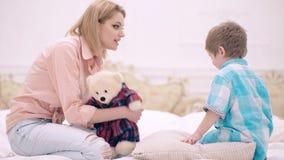 La maman et le petit garçon parlent dans la chambre à coucher sur le lit Concept de communication de famille Une famille heureuse banque de vidéos