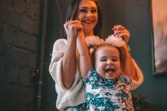 La maman et sa fille d'enfant de fille jouent, sourient et étreignent Vacances et unité de famille photos libres de droits