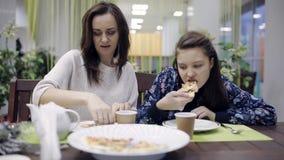 La maman et sa fille mangent de la pizza et du thé dans un café dîner à la pizzeria Nourriture malsaine en aliments de préparatio banque de vidéos