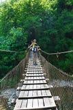 La maman et ses touristes de fils traversent la rivière de montagne sur le pont suspendu Image libre de droits