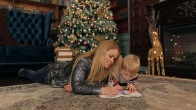La maman et son fils dessinent près de l'arbre de Noël banque de vidéos