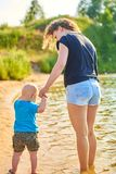 La maman et son fils marchent le long de la berge un jour chaud d'été photos stock