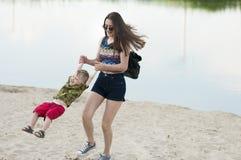 La maman et son fils ont l'amusement jouant sur le sable Image libre de droits