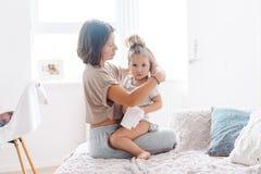 La maman fait des tresses à sa petite fille Image libre de droits