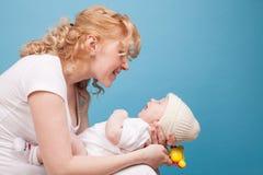 La maman garde en main un bonheur d'amour de fils de bébé Photographie stock libre de droits