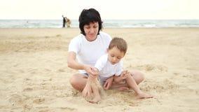 La maman heureuse et son bébé jouent avec le sable sur la plage de mer, dans le mouvement lent banque de vidéos
