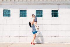 La maman jette la fille sur le fond blanc de mur de briques photos stock