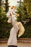 La maman jette un bébé rouge et rire, automne photo libre de droits