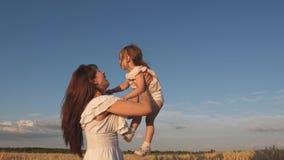 La maman jette une fille heureuse dans le ciel mère et petit jeu de bébé sur un champ de blé mûr Voyages heureux de famille banque de vidéos