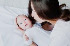 La maman joue avec le bébé tenant sa main et sourire Images libres de droits
