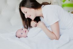 La maman joue avec le bébé tenant sa main et sourire Photographie stock libre de droits
