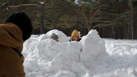 La maman, le fils et le papa jouent le combat de boule de neige dans le week-end de famille de forêt d'hiver banque de vidéos