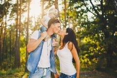 La maman, le papa et la fille de famille s'assied au papa sur les épaules, et au baiser de parents sur la nature dans la forêt pe Images libres de droits