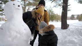 La maman, le papa et le fils heureux de famille font un bonhomme de neige en parc de ville d'hiver banque de vidéos