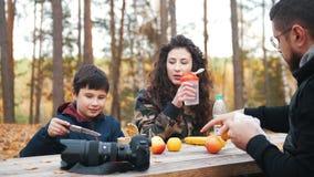 La maman, le papa et l'enfant s'asseyant dehors dans les bois à la table et apprécient le repas clips vidéos