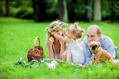 La maman, le papa, la blonde de petite fille et le chien se trouvent ensemble sur l'herbe a Photo stock