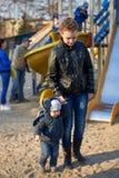 La maman mène son petit fils outre du terrain de jeu en raison du mauvais comportement image stock
