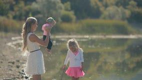 La maman marche avec ses petites filles mignonnes près du lac banque de vidéos