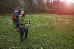 La maman marche dans la forêt avec un enfant, un enfant dans les enfants portent Photo stock