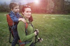 La maman marche dans la forêt avec un enfant, un enfant dans les enfants portent Photographie stock libre de droits