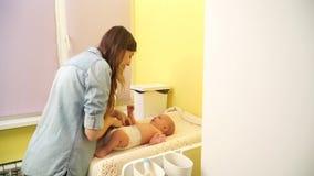 La maman met la couche-culotte de bébé banque de vidéos