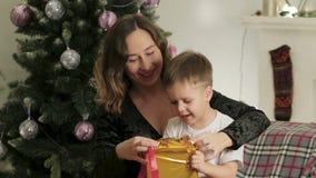 La maman mignonne, heureuse, enthousiaste et le fils déroulent un boîte-cadeau de Noël dans une belle salle banque de vidéos