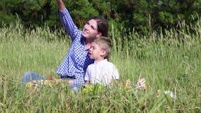 La maman montre la main vers le haut du petit garçon banque de vidéos