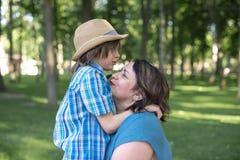 La maman ou la grand-mère calme tendrement un fils ou un petit-fils Photos libres de droits