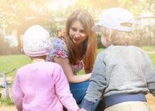 La maman parle aux jumeaux d'enfants et leur enseigne comment agir images stock