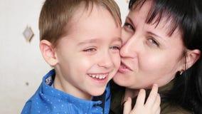 La maman prend soin du bébé pleurant, qui sourit alors clips vidéos