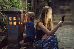 La maman regarde dans son smartphone, les regards de fils dans le c lumineux photographie stock