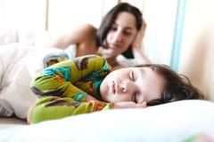 La maman regarde l'enfant de sommeil Photo stock