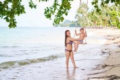 La maman roule son fils sur une oscillation sur le rivage de la baie - rivage arénacé, fond brouillé photographie stock