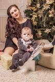 La maman s'assied sous l'arbre avec un petit enfant dans un boîte-cadeau Images libres de droits