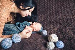 La maman s'est pliée plus d'à son bébé nouveau-né et a souri à lui photos stock