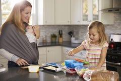 La maman tenant le bébé observe une fille plus âgée préparer la nourriture Image stock