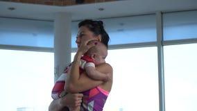 La maman tient l'enfant et bascule le sien de retour, pliant et détendant la position dans le gymnase pour le yoga banque de vidéos