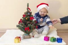 La maman tient la main d'un enfant contrarié dans un chapeau de Santa images stock