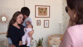 La maman tient sa fille dans des ses bras, et le papa se tient tout près Ils sont photographiés par un photographe clips vidéos