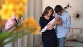 La maman tient sa fille dans des ses bras, et le papa se tient tout près Ils sont photographiés par un photographe banque de vidéos
