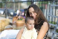 La maman tient un enfant dans des ses bras Une famille heureuse Jeune mère tenant son bébé dans des ses bras et frotté mon mother photo libre de droits
