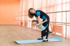 La maman tient une fille dans des ses bras exécutant une gymnastique d'exercice photographie stock