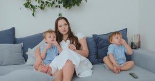 La mamma abbraccia i suoi due pochi figli sullo strato nel salone e guarda la TV Famiglia che guarda TV stock footage