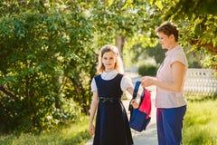La mamma aiuta la figlia a indossare uno zaino fotografie stock