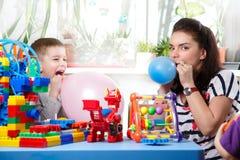 La mamma aiuta il figlio a gonfiare i palloni Fotografia Stock
