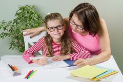 La mamma aiuta il suo allievo della scuola elementare della figlia in suo taccuino, Fotografia Stock Libera da Diritti