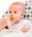 La mamma alimenta il bambino divertente dal cucchiaio fotografie stock libere da diritti